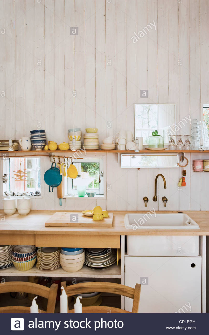 kitchenware on shelf above sink set in wooden worktop in country style CP1EGY
