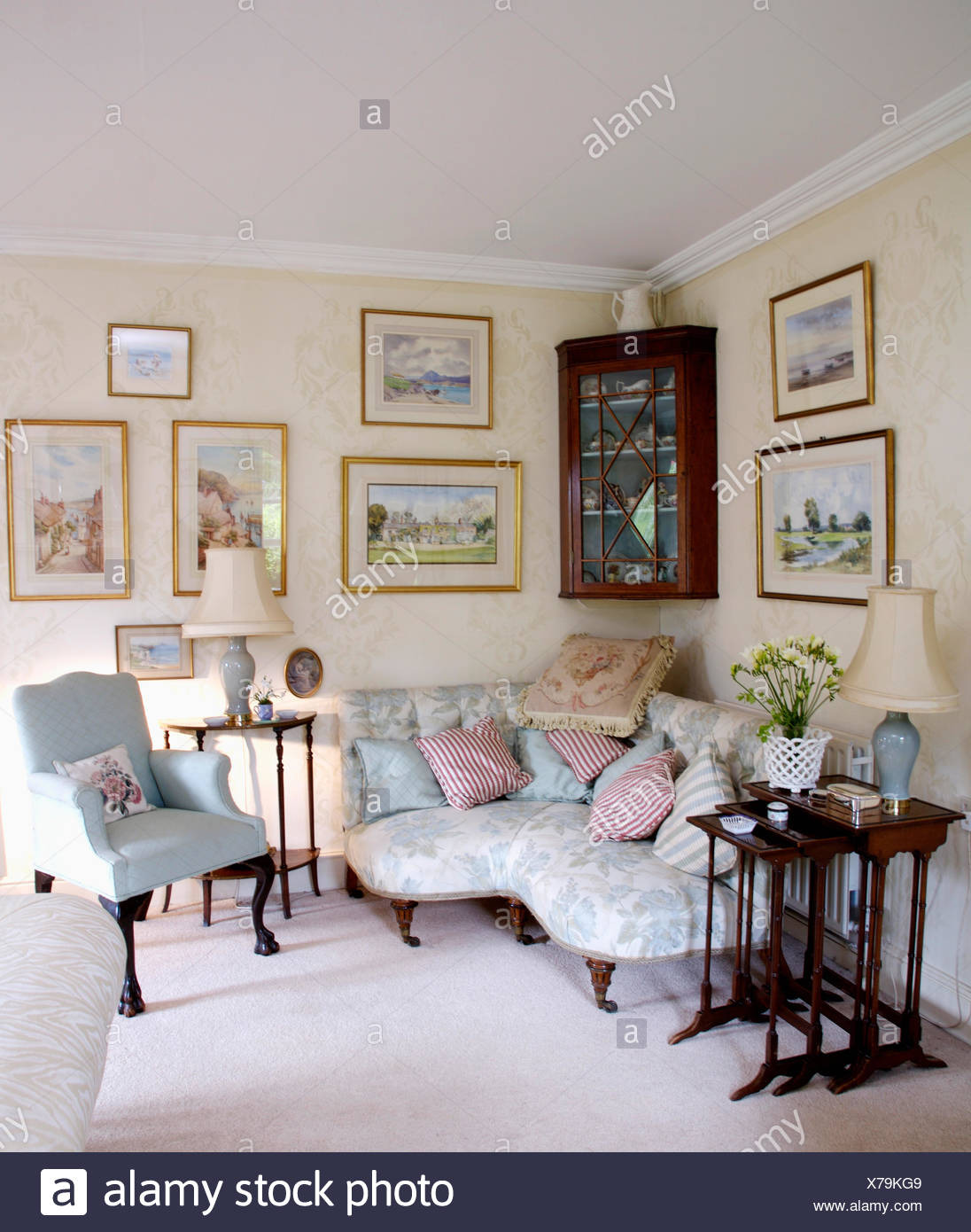 pictures above pale blue victorian corner sofa in country living sitting room with antique furniture and white carpet X79KG9