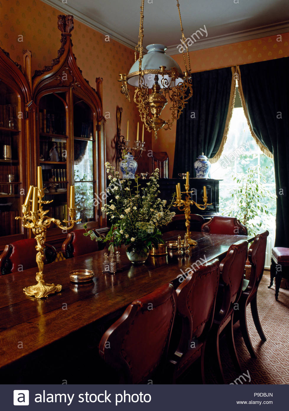 edwardian style glass and brass light fitting above an antique dining table with gilt candelabra in an old fashioned dining room P9DBJN