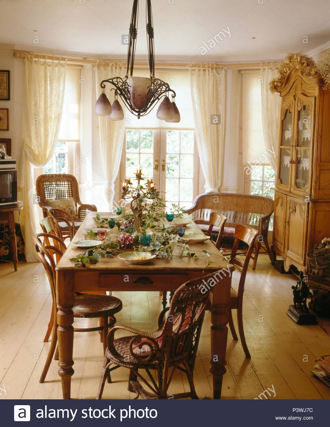 art nouveau style light above old pine table and vintage chairs in country dining room with wooden floor and white drapes P3WJ7C