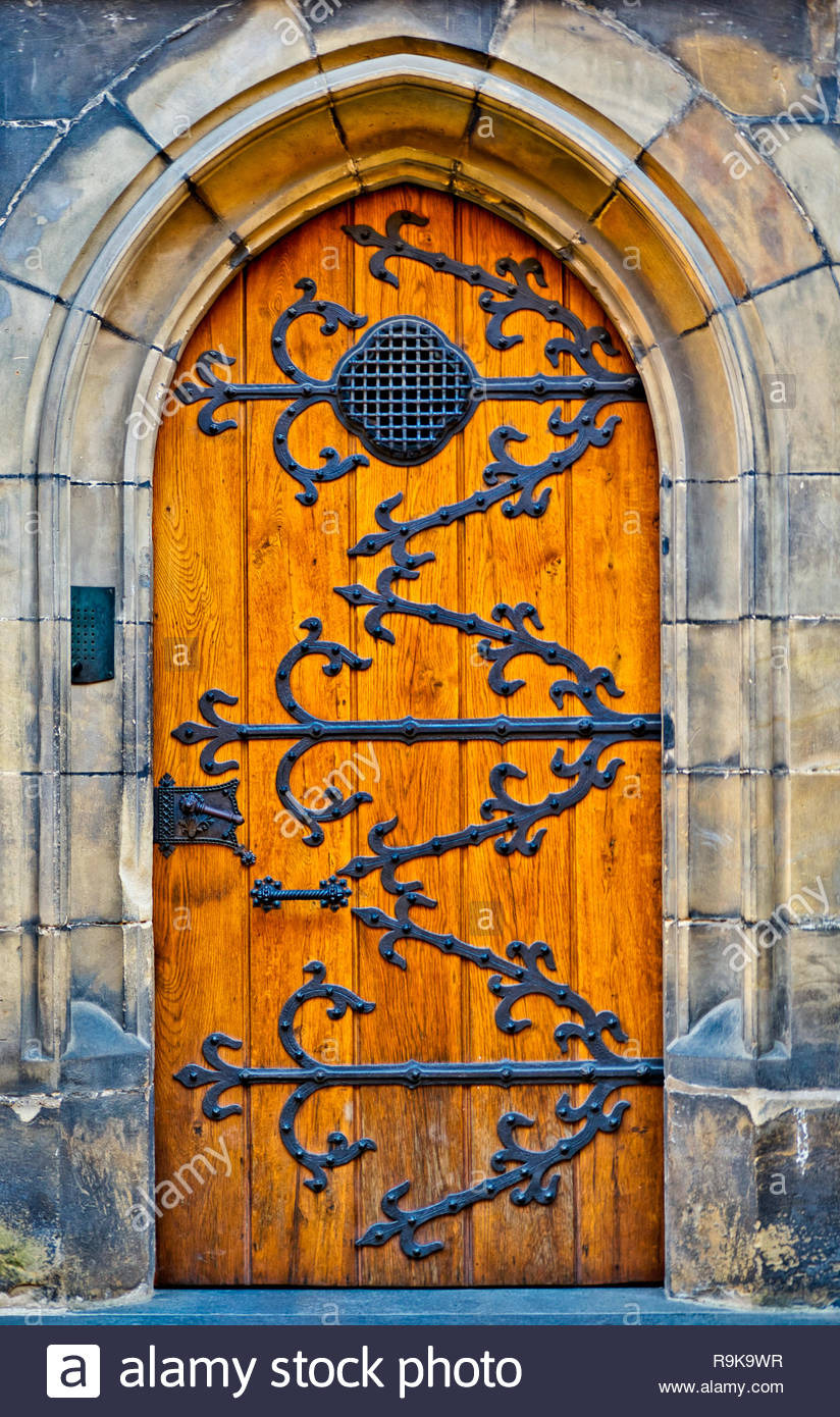 closed wooden door of ancient type with metal designs on it entrance gate of a castle with stone wall bright orange tone concept of opportunity fate R9K9WR