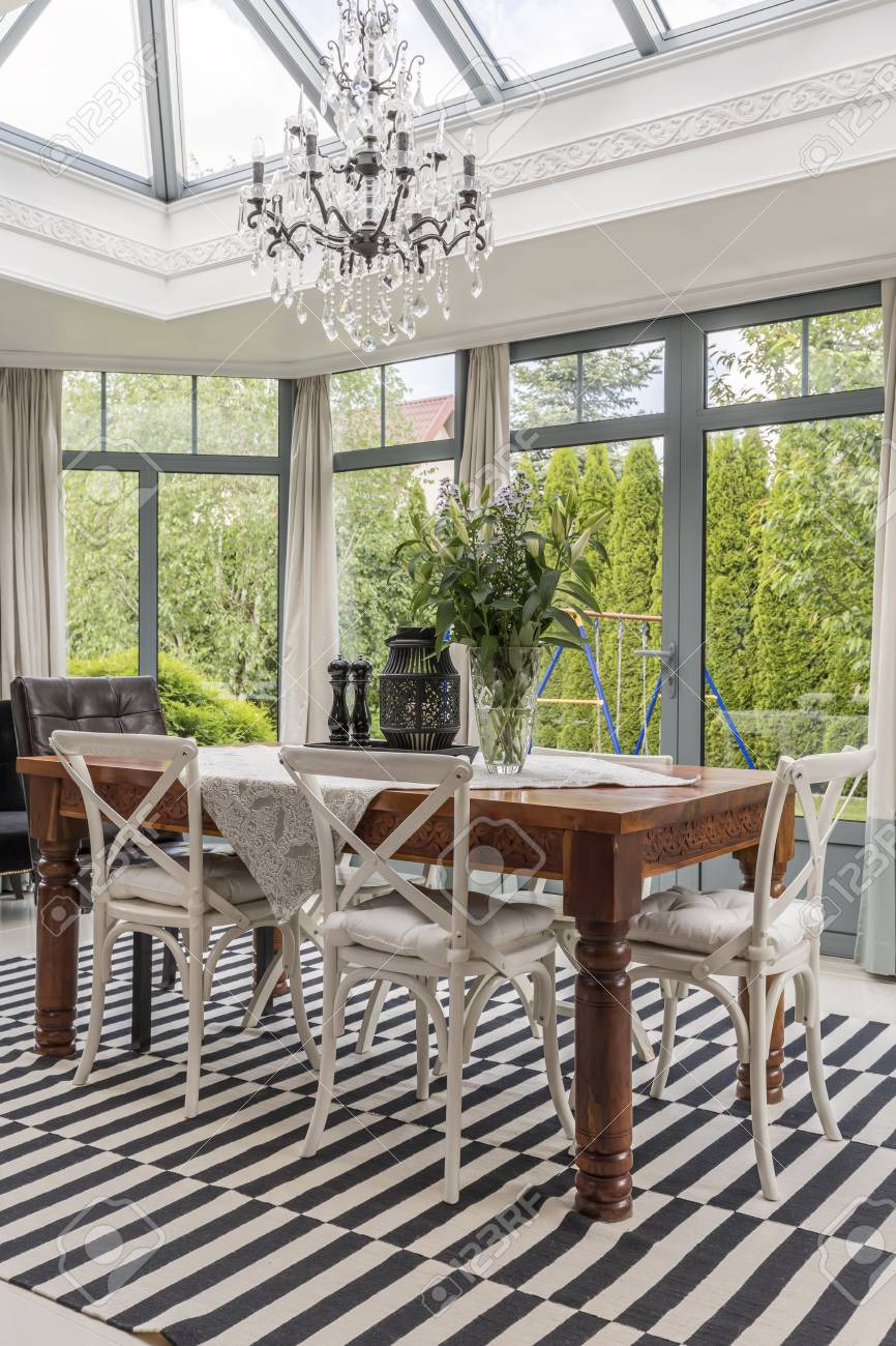 photo hardwood antique dining table with white chairs in orangeria with large windows