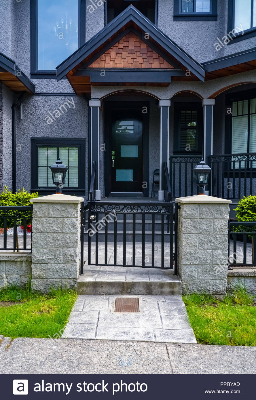 entrance of residential house with metal grid gate in front dark colored house with entrance gate PPRYAD