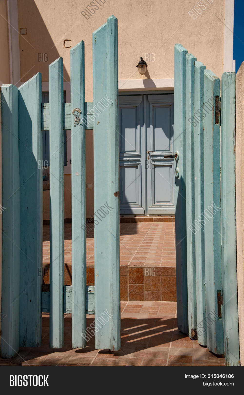 stock photo typical greek house entrance, with green gate and entrance door in the village of oia on the island