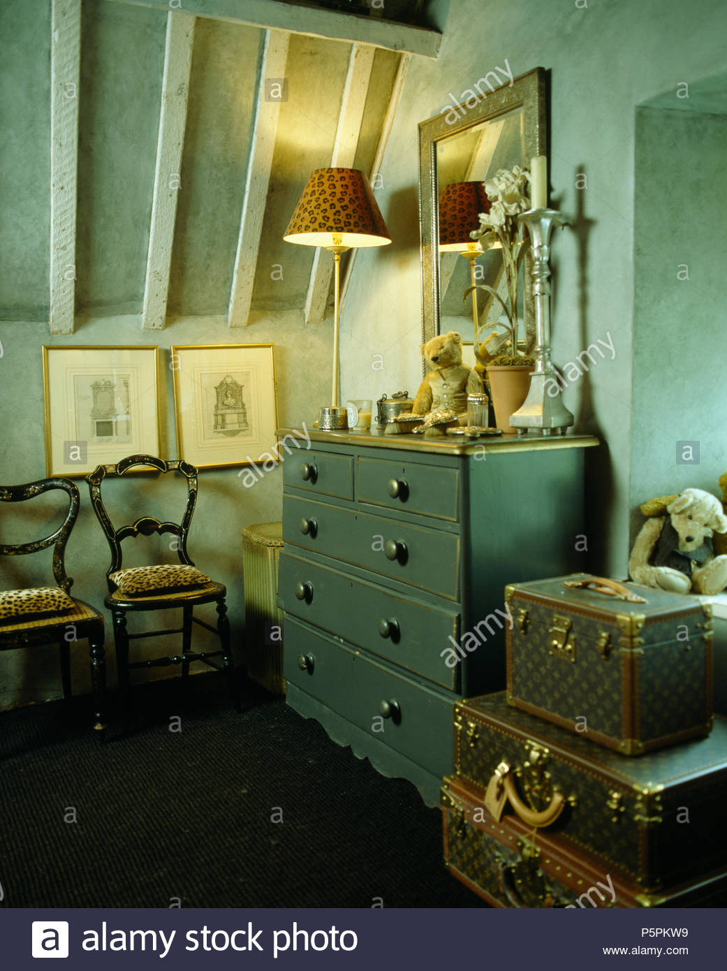 painted chest of drawers and antique chairs in pale turquoise attic room with stack of vintage suitcases P5PKW9