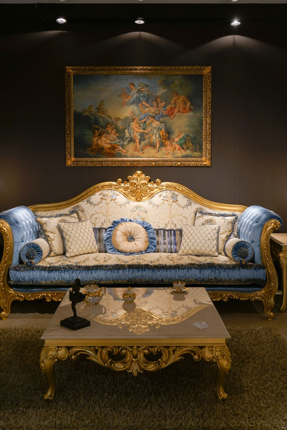 rococo blue sofa with gold frame and coffee table with a baroque design framed wall art above sofa