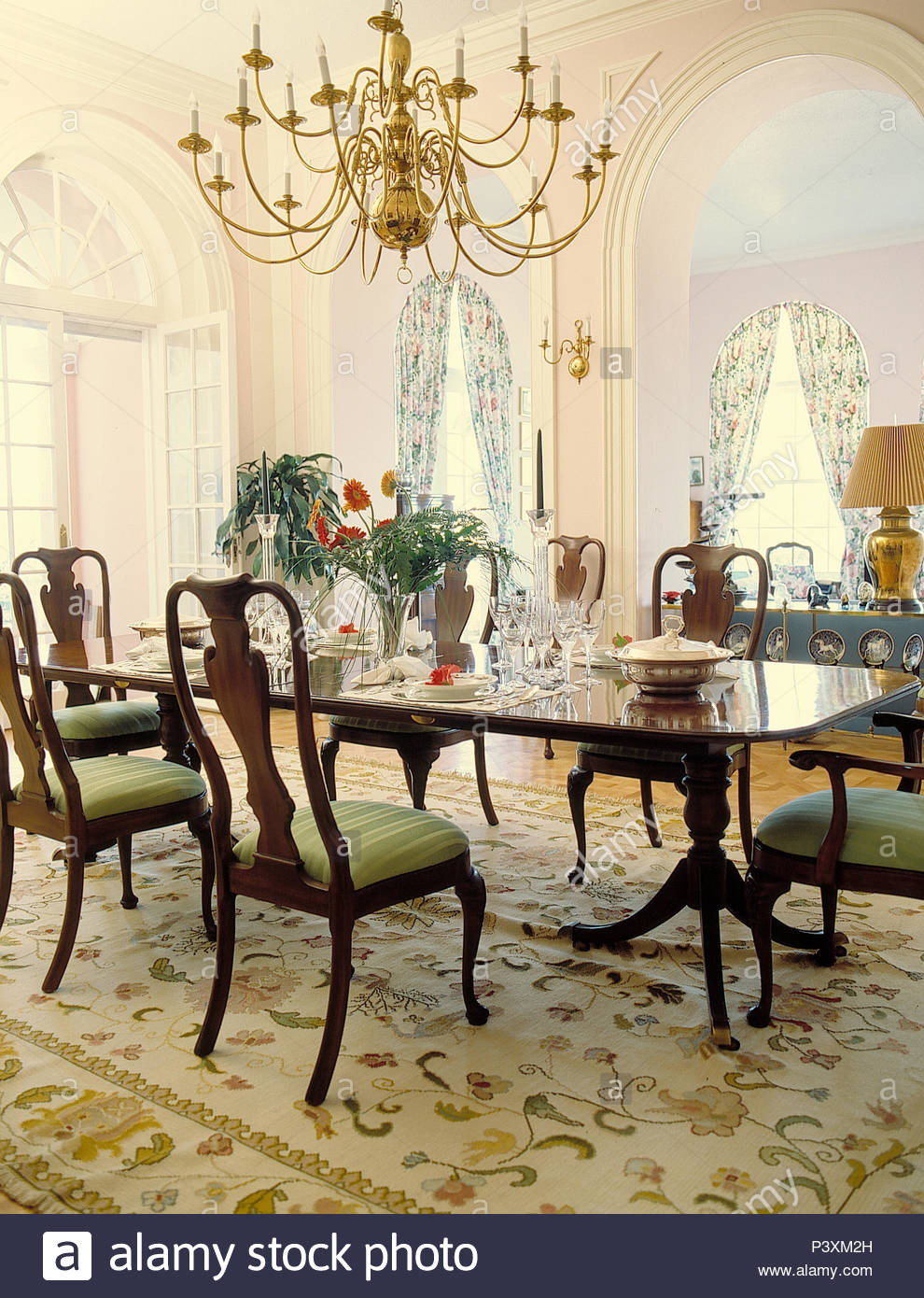 chandelier over antique mahogany dining table and chairs in opulent dining room with pale patterned rug P3XM2H