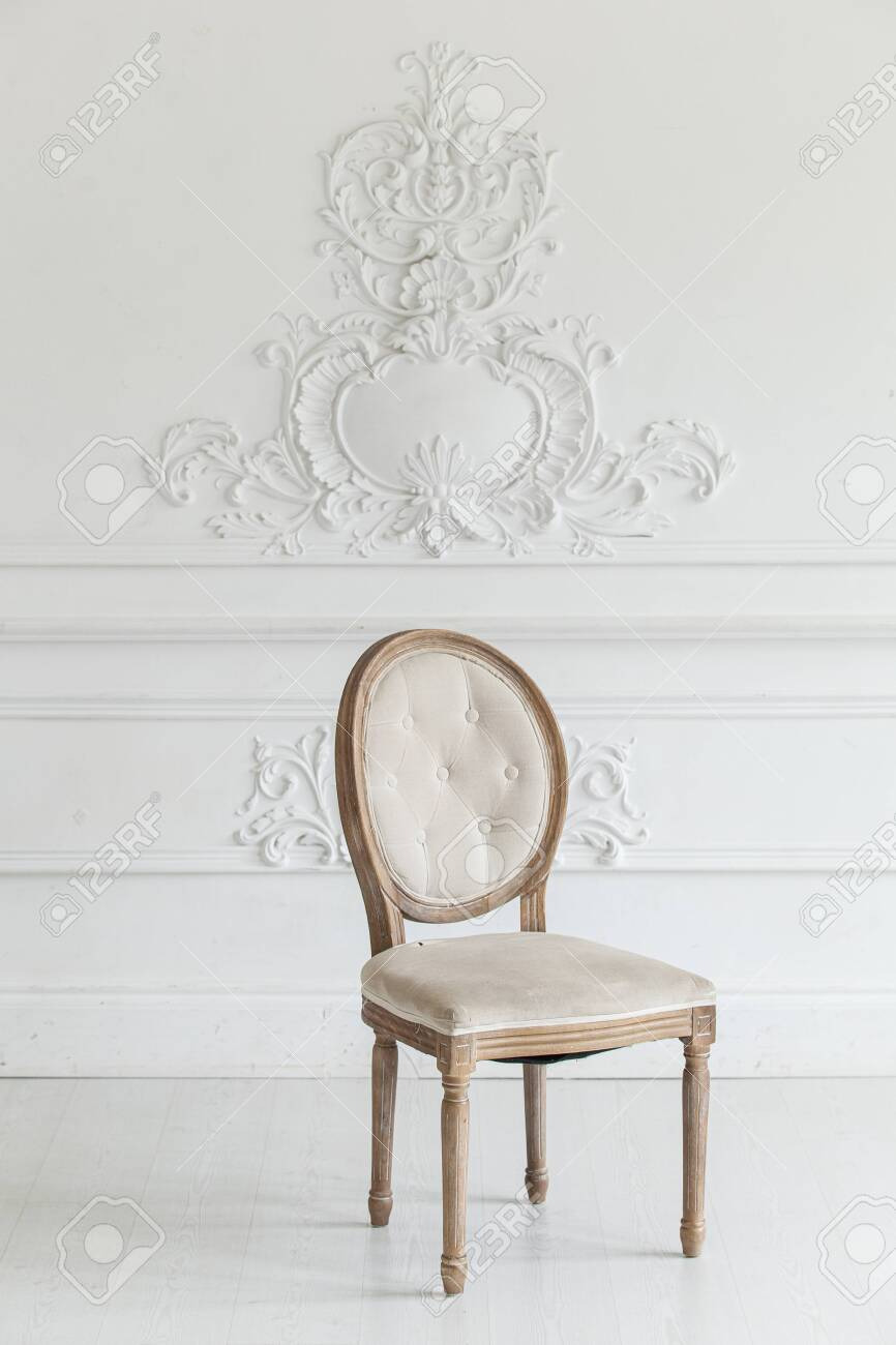 photo living room in antique style vintage chair against the wall with a bas relief of plaster stucco sele