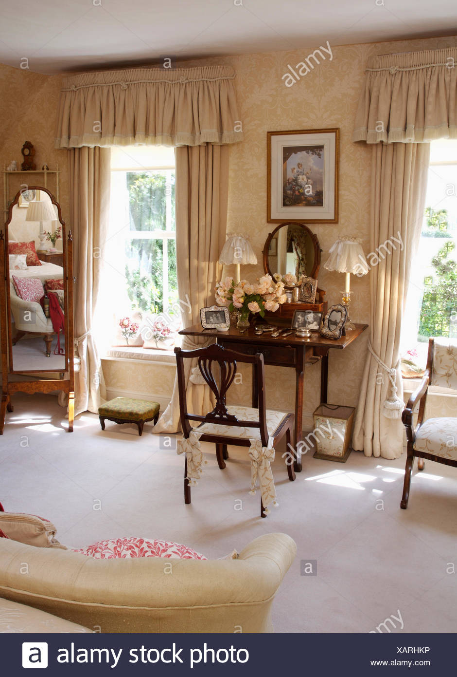 white carpet in cream country bedroom with antique furniture and cream curtains at tall windows XARHKP