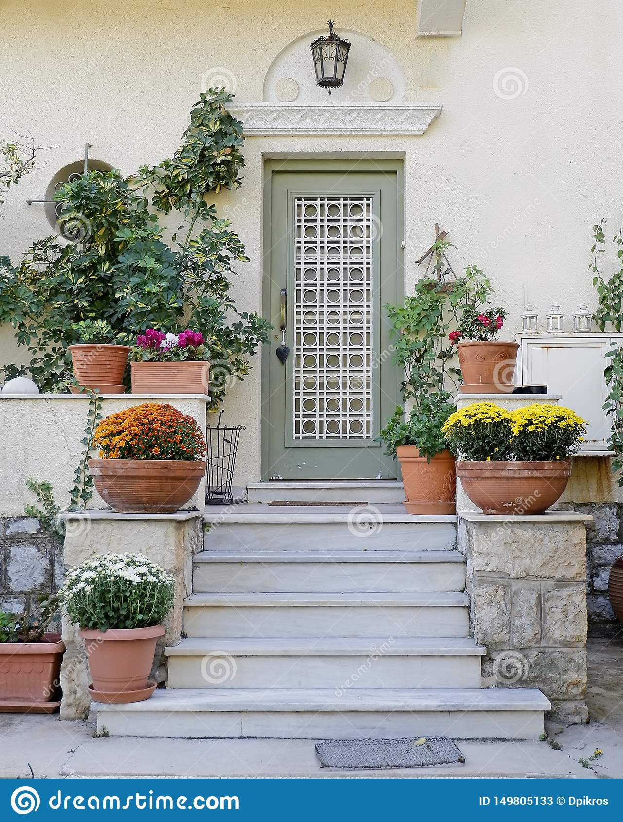 elegant house entrance stairs olive green door lots flower pots athens greece