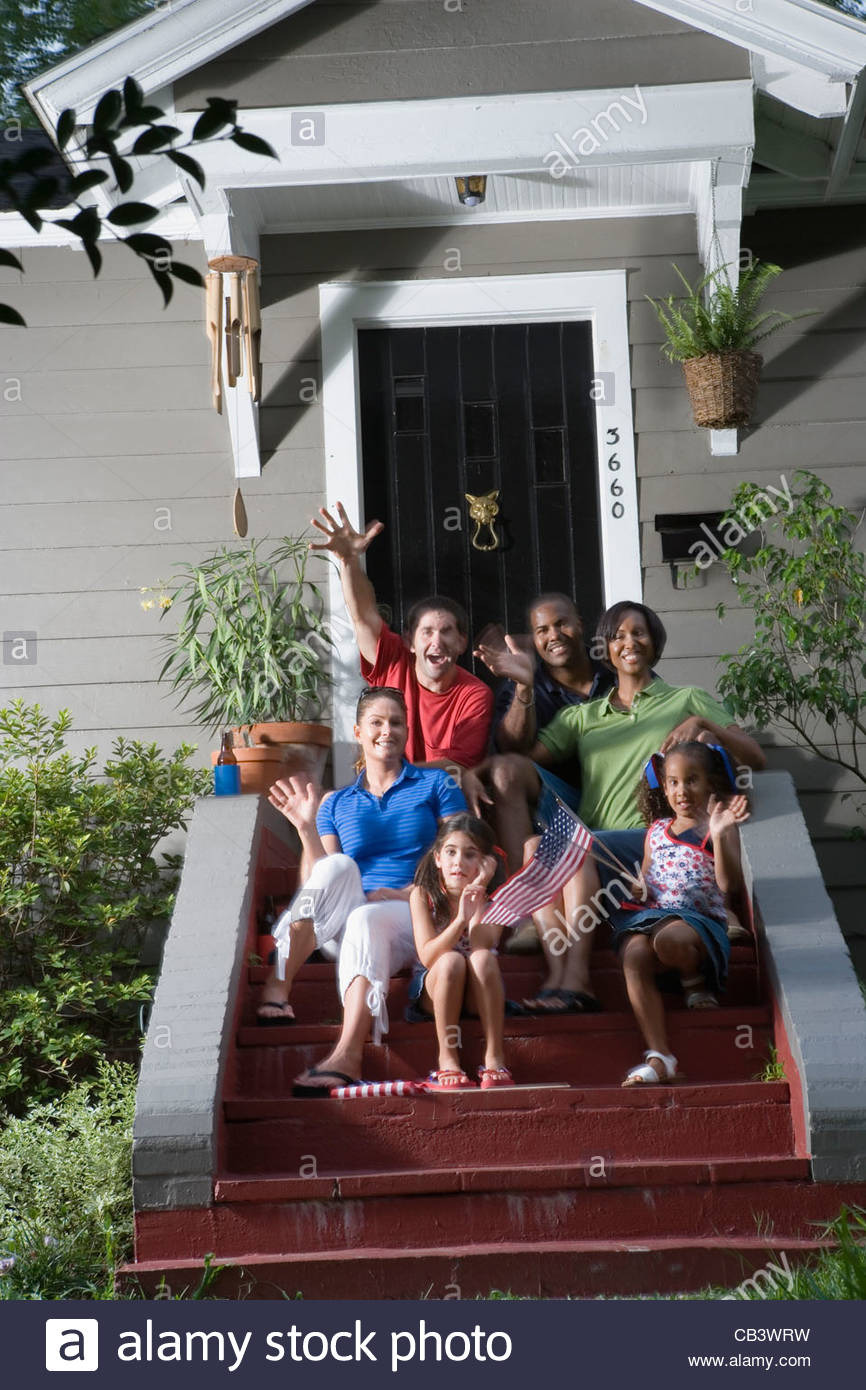 portrait of two families sitting on the front steps of a house waving CB3WRW