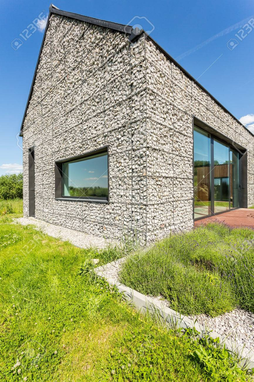 photo modern pebble stone wall house with large windows surrounded by wild grass