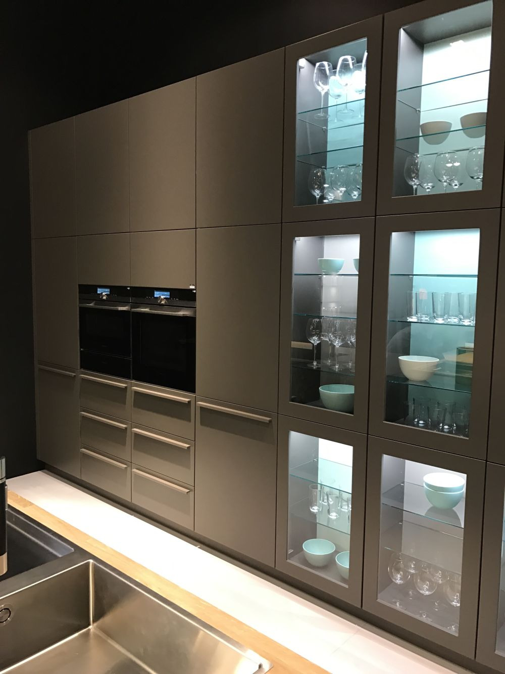 full wall kitchen cabinets in grey with built in appliances and clear glass doors led lighting behind