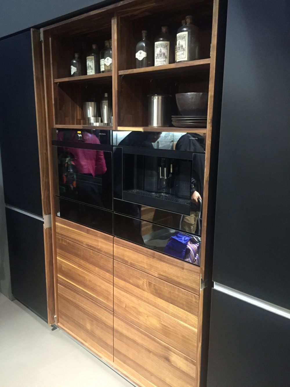 Black kitchen with pocket doors that help to hide appliances