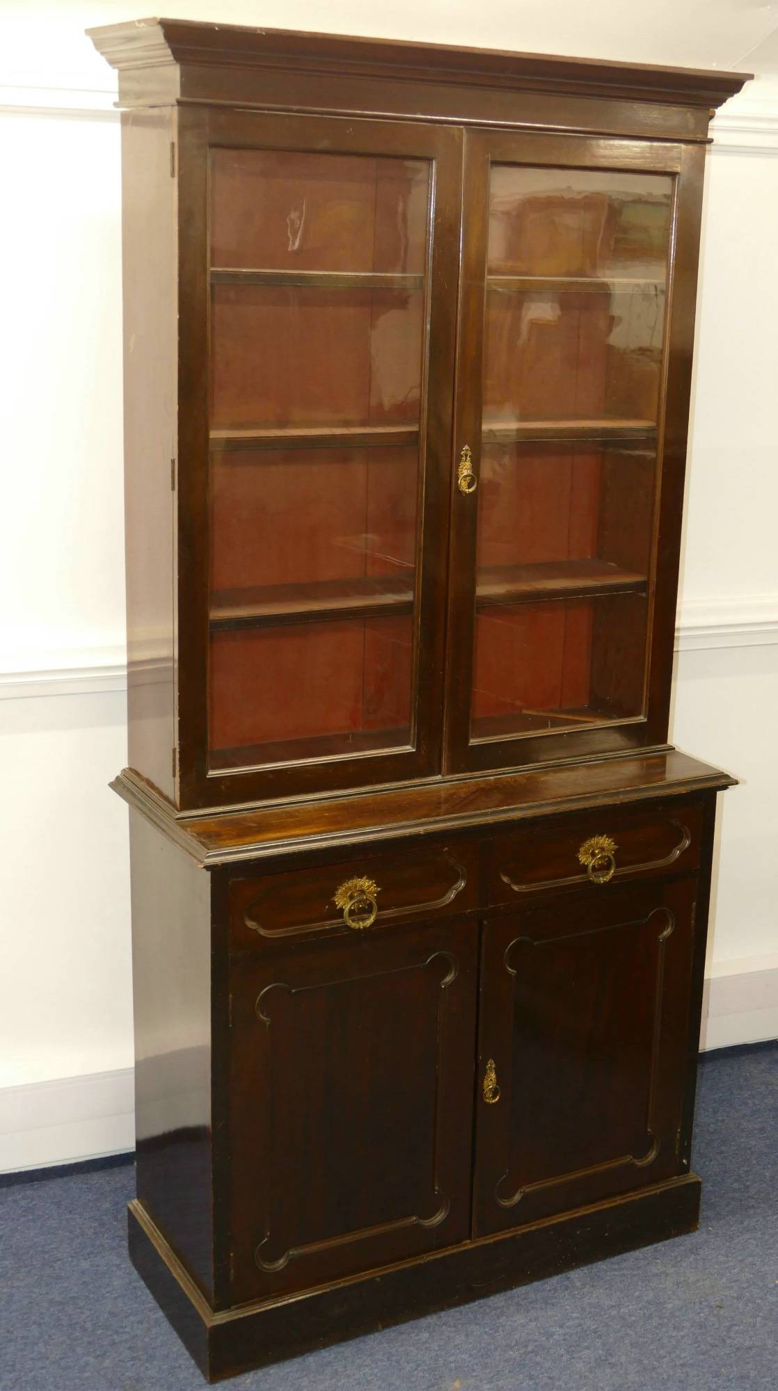 an edwardian mahogany display cabinet having 2 glass panelled doors enclosing adjustable shelves 2 short drawers and 2 further panelled doors below with drop brass ring handles 1m 7cm wide 2m 23cm high