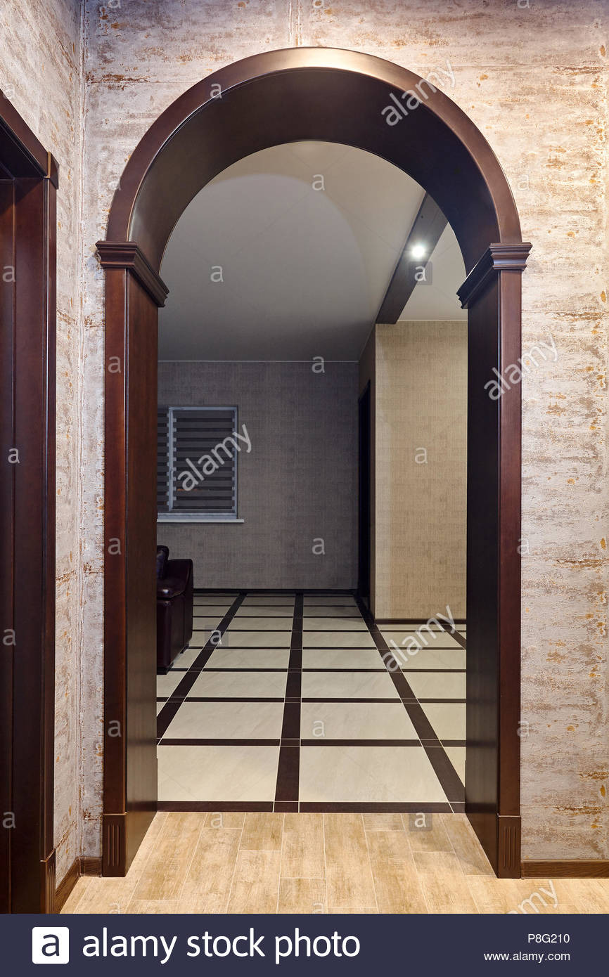 passing through a wooden arch into the living room decorated with brown tones an example of a modern home interior P8G210
