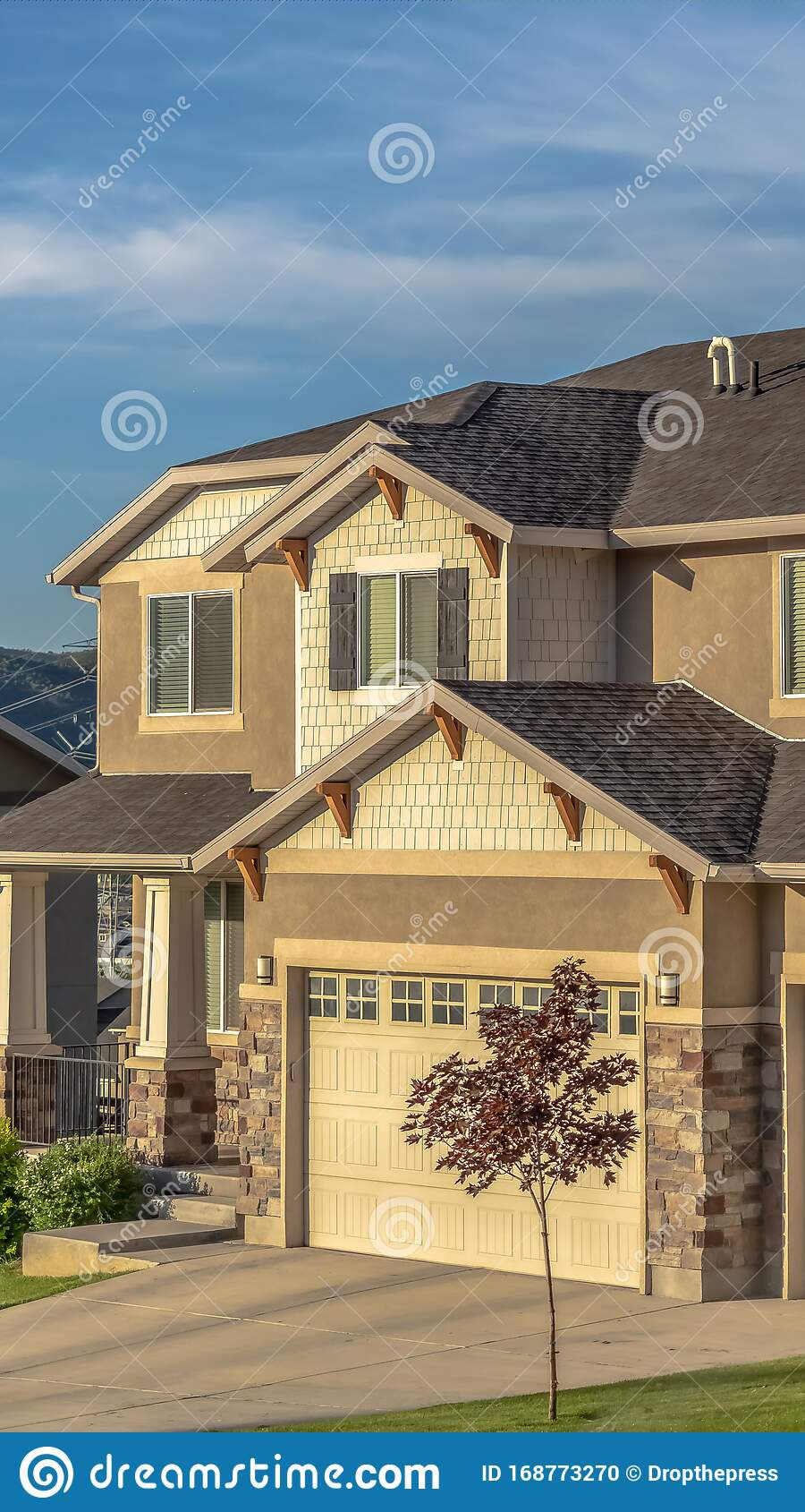 vertical beautiful house exterior concrete stone brick wall against blue sky gable dormer roofs garage dors driveway