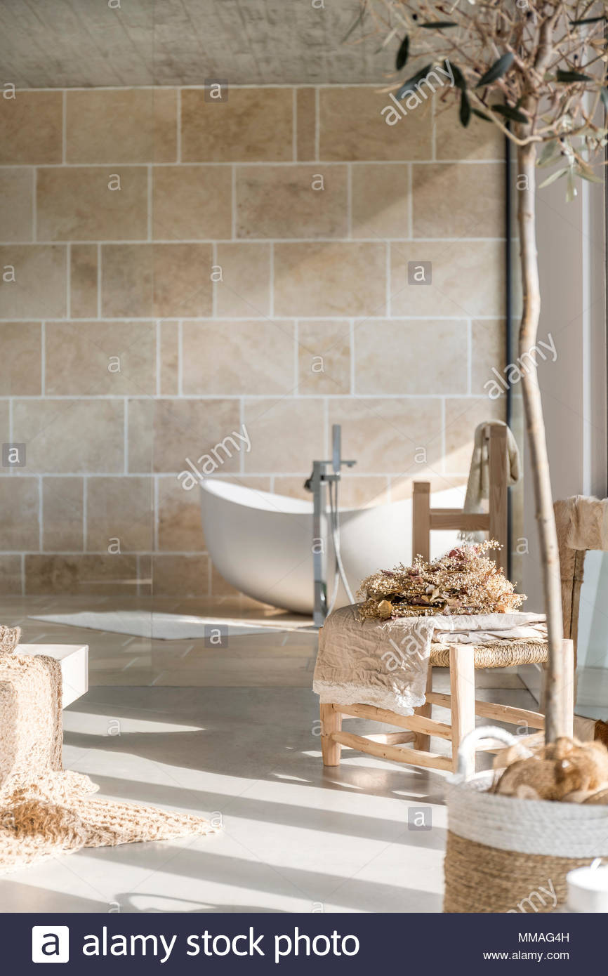trendy bathroom with white bathtub and wooden decorative accessories MMAG4H