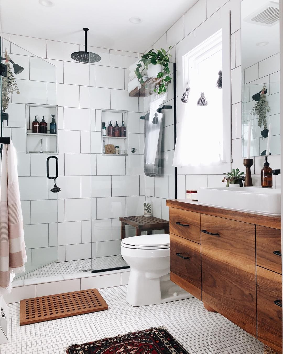 Bathroom with walk in shower and large white tiles wood cabinets