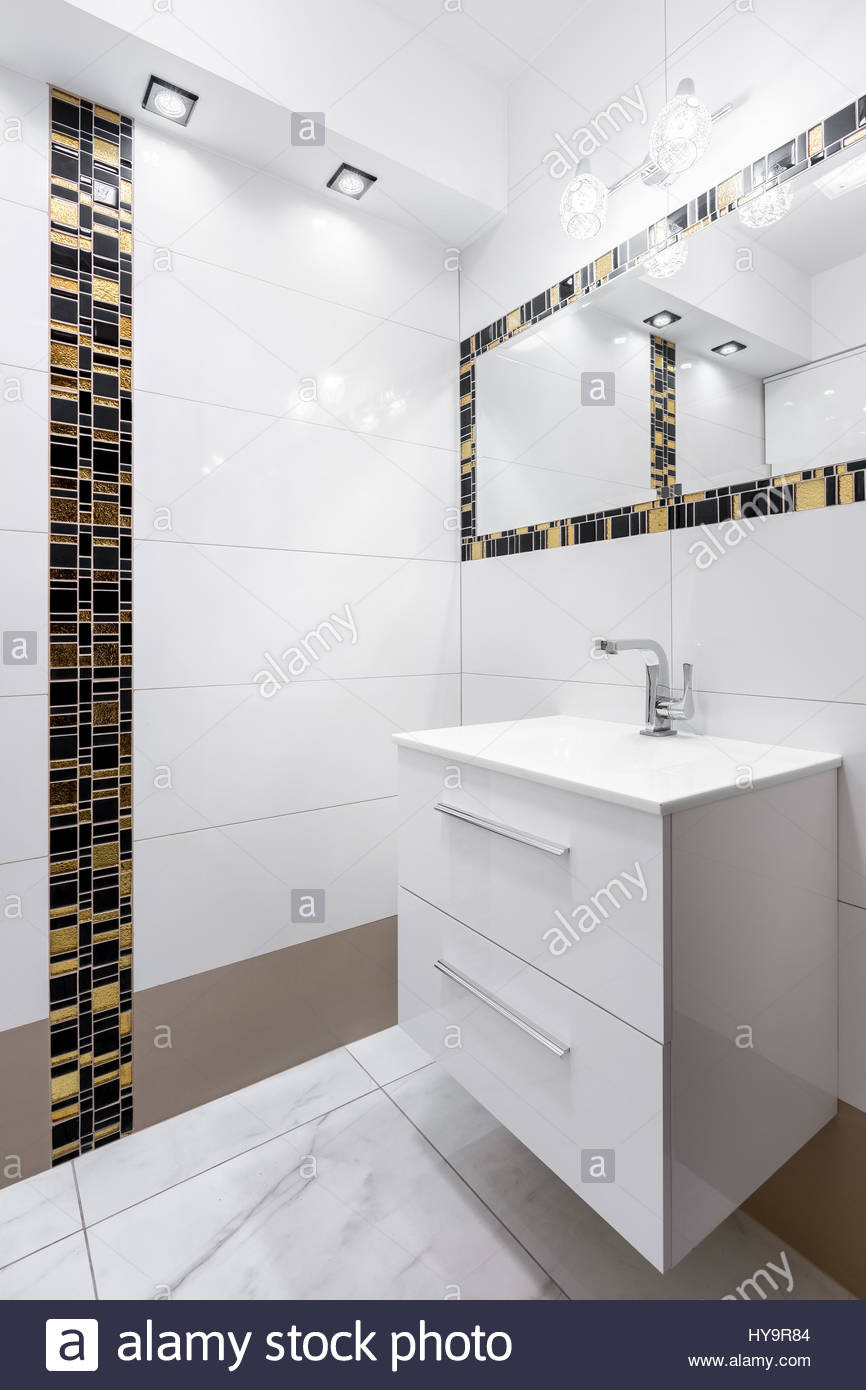 white bathroom with decorative black and gold tiles on wall and around HY9R84