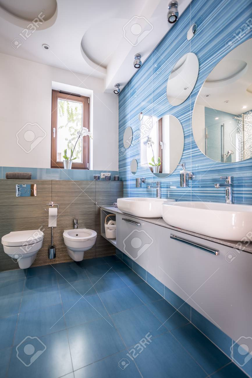 photo contemporary bathroom with blue decorative tiles and round mirrors