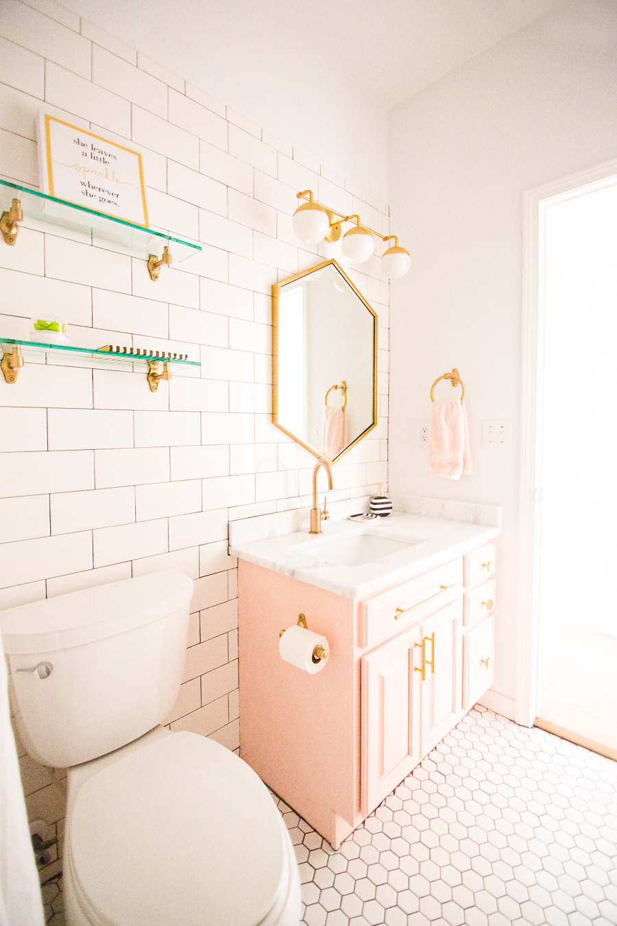 Modern Glam Blush Girls Bathroom Design gold hexagon mirror blush cabinets gold hardware white hexagon floor glass shelves pink bathroom cabinets gold orb sconce 1 1