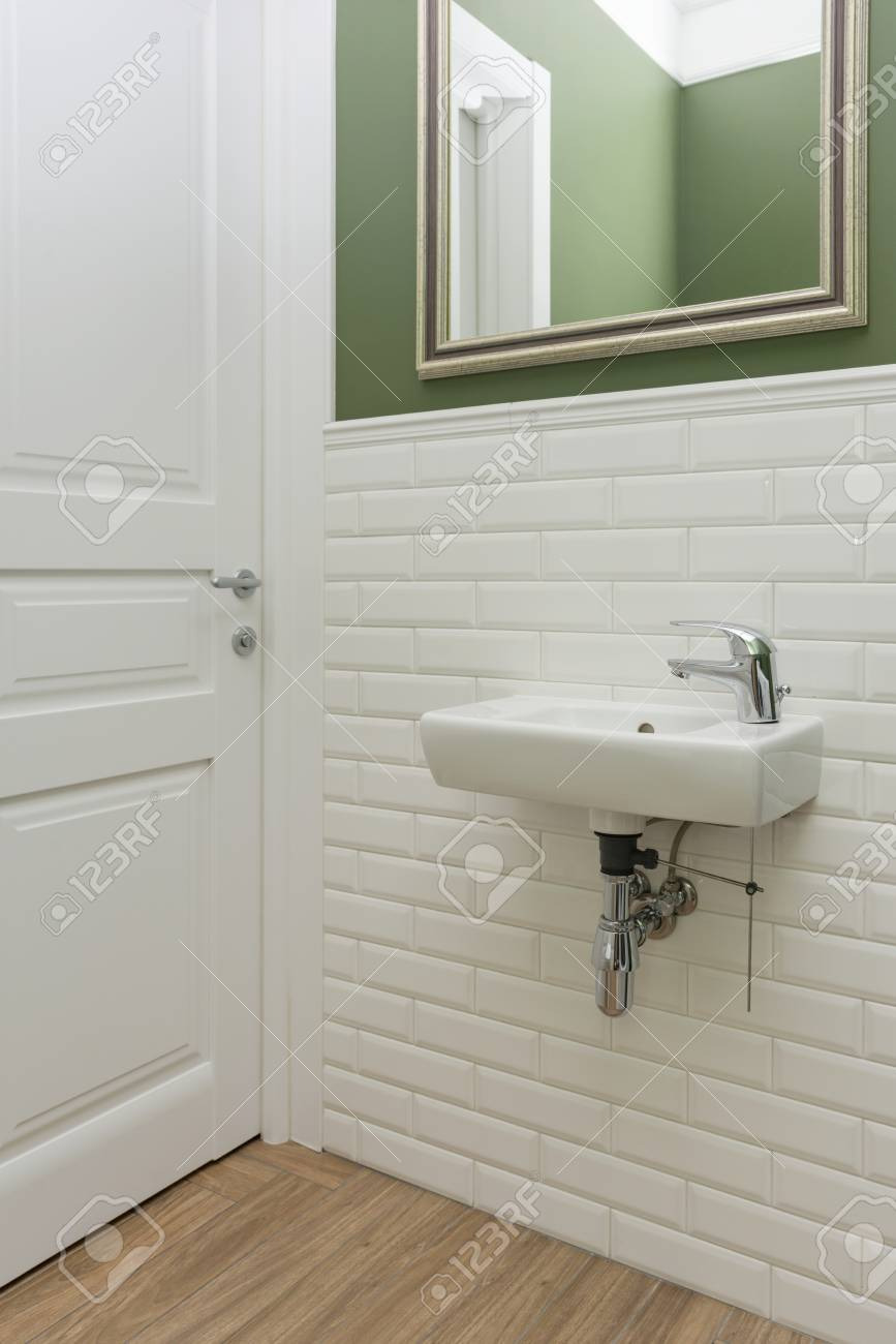 photo bathroom toilet room interior close up the walls are painted green covered with decorative ceramic t